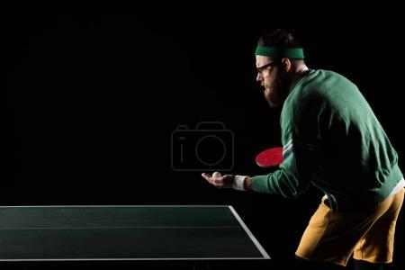 side view of bearded tennis player with tennis racket and ball standing at table isolated on black