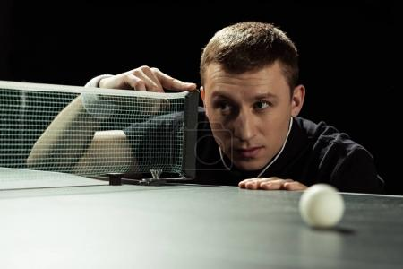 portrait of focused tennis player checking net on tennis table isolated on black