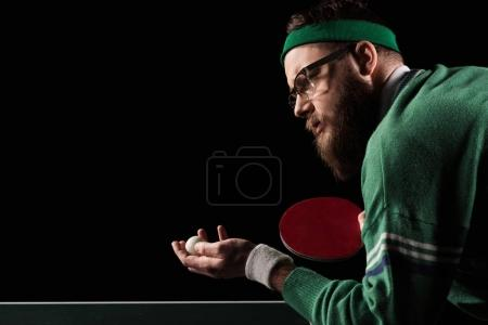 Photo for Side view of bearded tennis player with tennis racket and ball isolated on black - Royalty Free Image