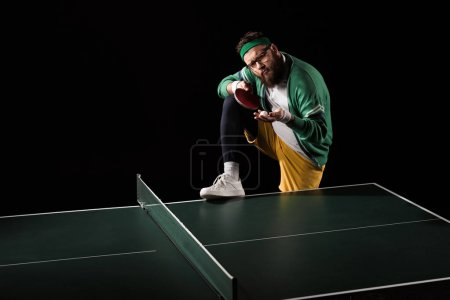 bearded sportsman with tennis equipment standing at table isolated on black