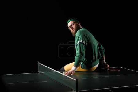 back view of bearded tennis player sitting on tennis table isolated on black