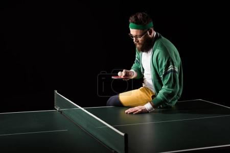 bearded tennis player with racket and ball sitting on tennis table isolated on black