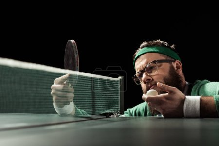 pensive bearded tennis player looking at racket in hand isolated on black