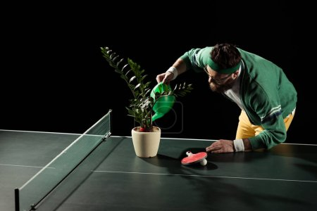 bearded tennis player watering flower in pot on tennis table isolated on black