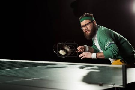 tennis player with frying pan with egg playing table tennis isolated on black