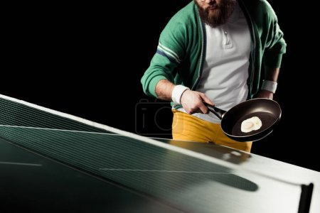 partial view of tennis player holding frying pan with egg in hand at tennis table isolated on black