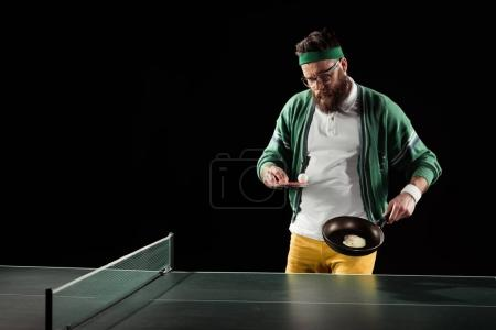 bearded sportsman with tennis equipment and egg on frying pan isolated on black