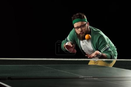 tennis player throwing up mandarin at tennis table isolated on black