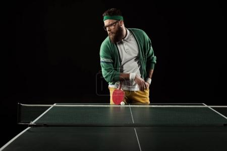 bearded tennis player leaning on racket on tennis table isolated on black