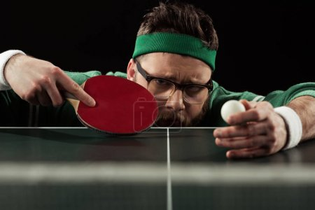tennis player with tennis racket and ball at tennis table isolated on black