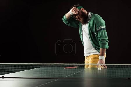 tired tennis player neat tennis table isolated on black