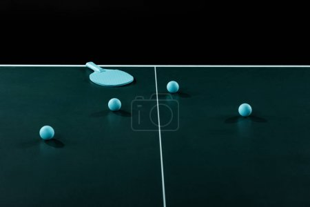 close up view of blue tennis racket and balls on tennis table isolated on black