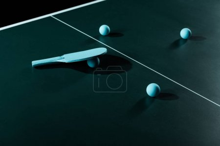 close up view of blue tennis racket and balls on tennis table