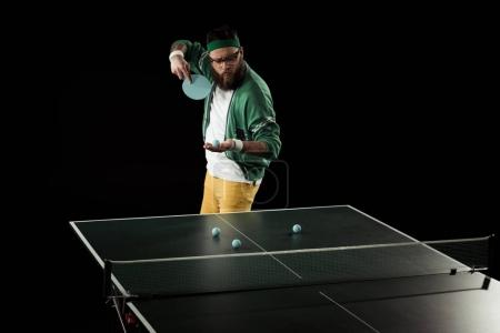 bearded tennis player practicing in table tennis isolated on black