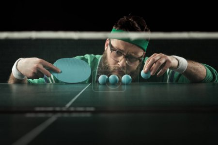 bearded tennis player looking at blue tennis balls on table isolated on black