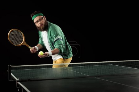 sportsman playing table tennis alone isolated on black