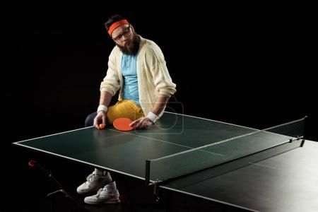 thoughtful tennis player sitting on tennis table isolated on black