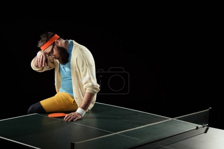 tired tennis player sitting on tennis table isolated on black