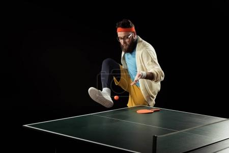 bearded tennis player playing with ball near tennis ball isolated on black