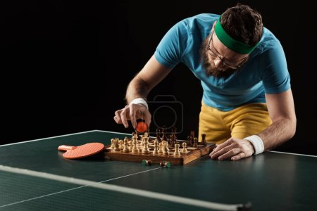 tennis player putting ball on chess board on tennis table isolated on black