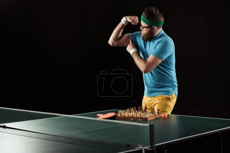 tennis player showing muscles while standing at tennis table with chess board isolated on black