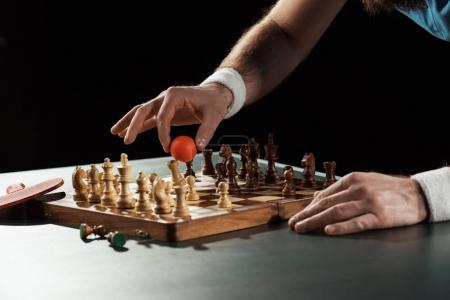partial view of tennis player putting tennis ball on chess board with figures isolated on black