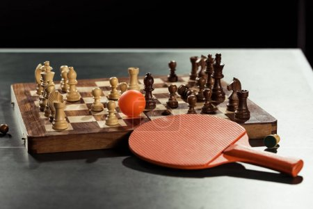 close up view of tennis racket, ball and chess board with figures on tennis table