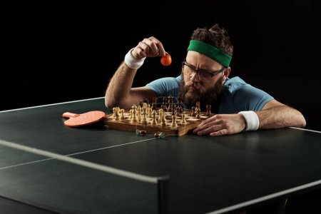 bearded sportsman throwing tennis ball on chess board on tennis table isolated on black