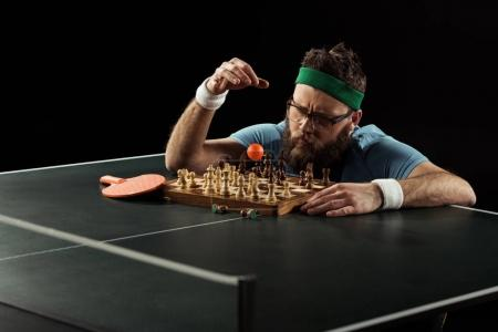 focused bearded tennis player throwing ball on chess board on tennis table isolated on black