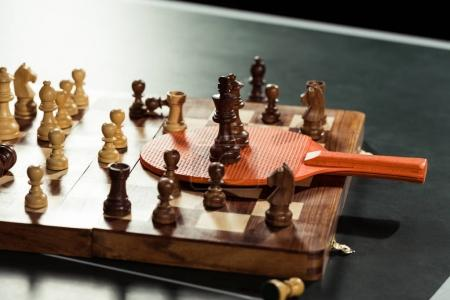close up view of tennis racket and chess board with figures on tennis table