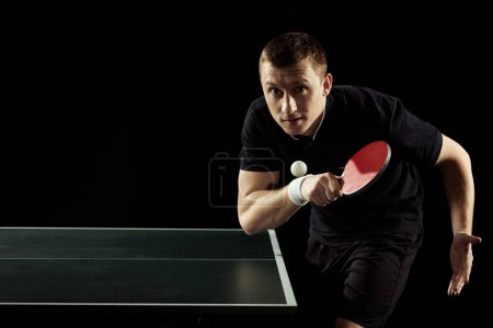 portrait of focused tennis player playing table tennis isolated on black
