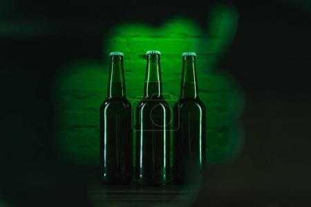 selective focus of green bottles of beer near green brick wall