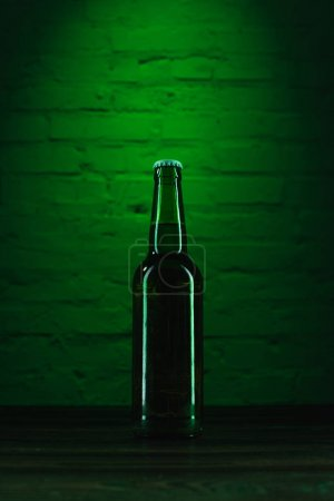 close-up view of single green beer bottle in green light