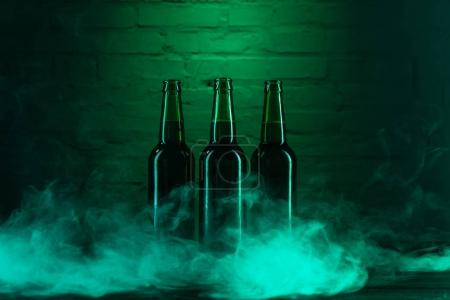 three green beer bottles and smoke near green brick wall