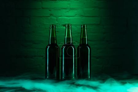 three open green beer bottles and smoke in green light