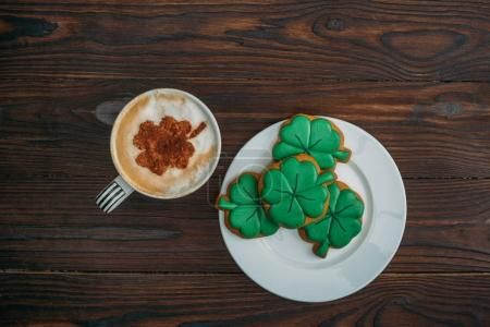 top view of tasty cappuccino and cookies in shape of clovers on wooden table