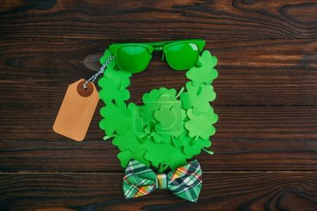 top view of bearded face symbol made of green clovers, sunglasses, blank tag and bow tie on wooden table