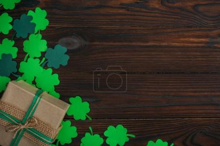 top view of wrapped gift box and green shamrocks on wooden table