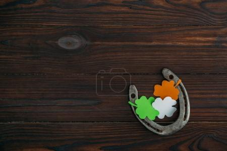 top view of horseshoe and clovers in colors of irish flag on wooden table