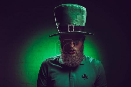 portrait of bearded young man in green irish hat and funny eyeglasses