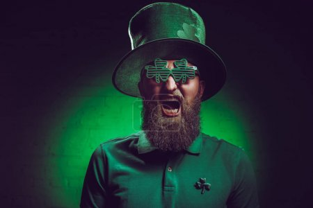 bearded man in green irish hat and funny eyeglasses screaming at camera