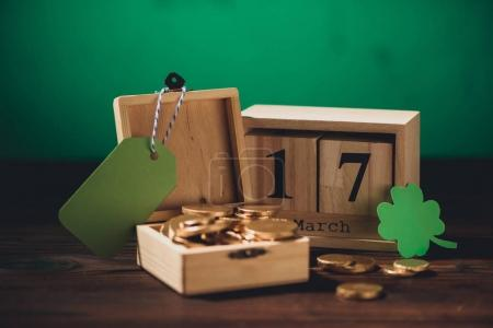 close-up view of calendar, green shamrock symbol, blank label and golden coins on wooden table