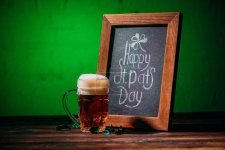 wooden frame with happy st patricks day inscription and glass of beer on table