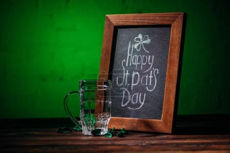 wooden frame with happy st patricks day inscription and empty beer glass on table
