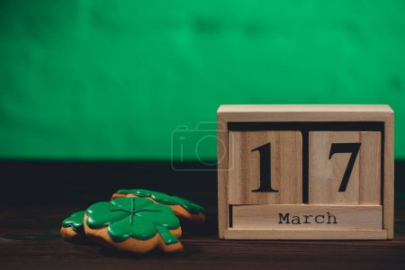 close-up view of calendar with 17 march date and cookies and hsape of shamrocks on wooden table top
