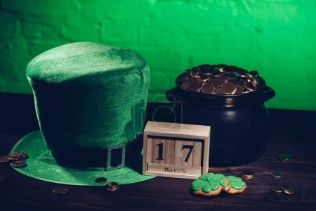 calendar, cookies in shape of shamrock, green irish hat and pot with golden coins on wooden table