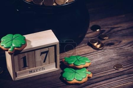 close-up view of calendar, cookies in shape of shamrock and pot with golden coins on wooden table