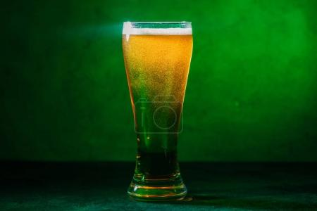 close-up view of glass with fresh cold amber beer on green