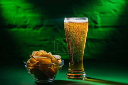 close-up view of glass with fresh cold beer and potato chips in bowl