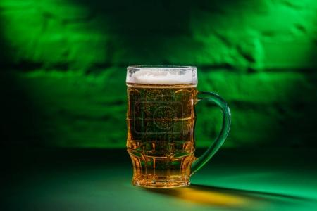 close-up view of cold beer in glass in green light